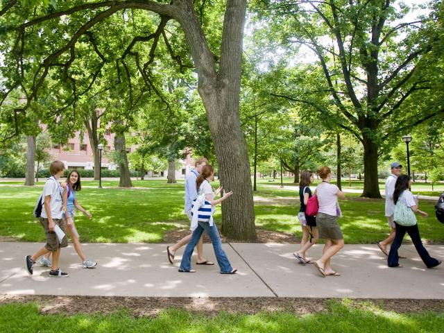 Students walking on sidewalk.