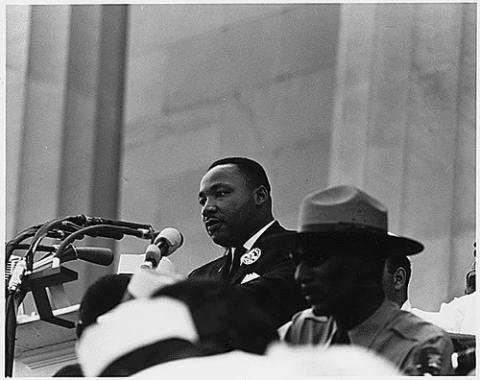 Black and white photo of Martin Luther King, Jr. who can be seen over the heads of a few other people. He is learning towards a microphone as if he is giving a speech.