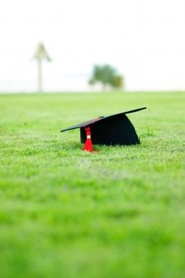 Graduation cap with a red tassel on an area of bright green grass