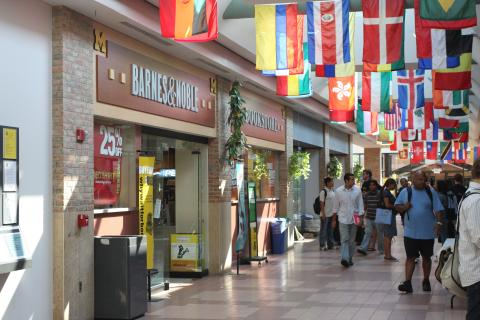Photo of people walking down the hall that includes with bookstore and several flags representing multiple countries hanging from the ceiling in Pierpont Commons