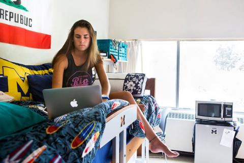 Woman sitting on bed in Residence Hall Room