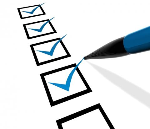 """Image of checklist being marked with """"checks"""" by a blue pen that is writing the check marks in blue ink. 4 of the 5 boxes on the list have been checked."""