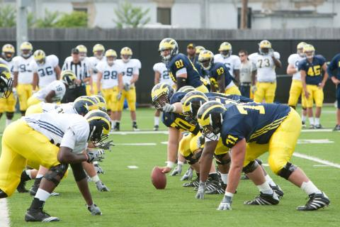 Football players lined up facing each other, half in navy jerseys and half in white jerseys, the group with the navy jerseys have the ball