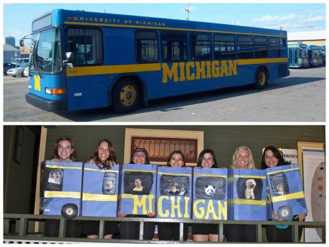 """Two Pictures. Top is a blue bus with a yellow stripe down the side that reads Michigan. Below is a group of students stressed up as a blue bus all standing in a line with various pictures cut out of people """"riding"""" in costume bus."""