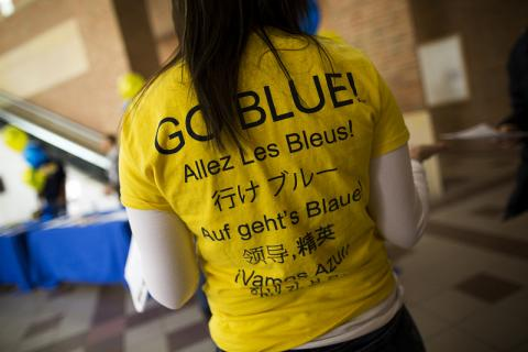 "A woman wearing a ""Go Blue"" shirt that says the phrase in different languages"