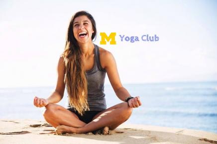 "A person with long brown hair sitting cross-legged on a beach in a grey tank top and black shorts while laughing. There is water in the background and blue sky. Next to the person's head it reads ""Yoga Club"" with a block M"