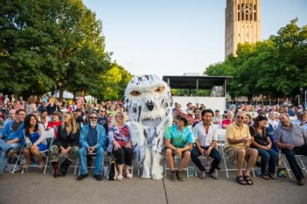 Group of people at Ann Arbor Summer Festival with a person in a large owl mascot costume