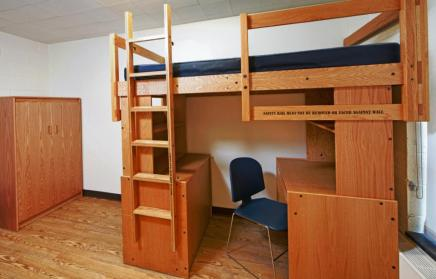Red/Brown wooded Lofted residence hall bed and desk arrangement in an otherwise empty dorm room.