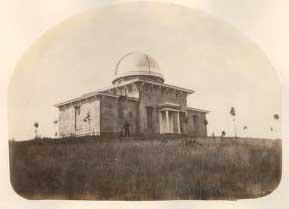 Sepia tone photo of the Detroit Observatory; a dome shaped building on UM's campus with flags on it's perimeter