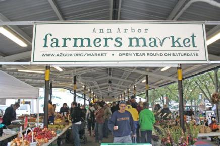 Famers Market sign with a white background and green letters posted above the farmers market. Below are people shopping at different tables full of fruits and vegetables.