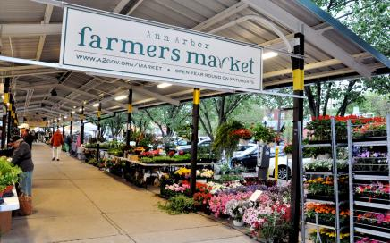 "Photo of an overhang covering beds of colorful flowers with a sign that reads ""Farmers Market"""