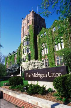 "The Michigan union with a bright sunny sky in the background. You can see the brown sign in front of the building that reads ""Michigan Union"". There is bright green moss growing up the outside walls."