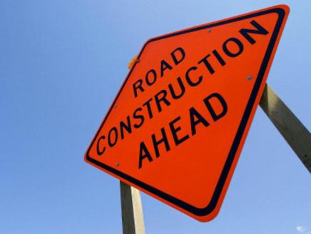 """Bright orange Sign that reads """"Road Construction Ahead"""" with blue sky in the background"""