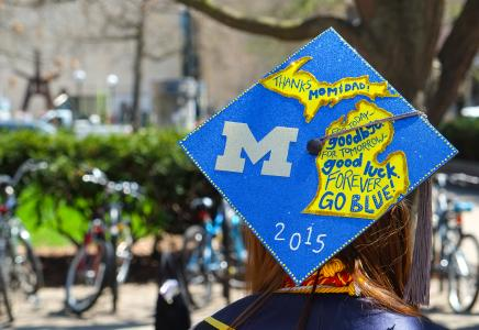 Grad cap painted in blue with the shape of the state of Michigan in Maize