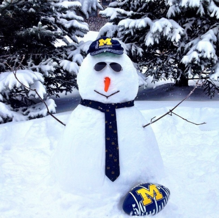 Snowperson with a Michigan football, a dark blue tie, and a Michigan hat. There are snowy pine trees in the background.