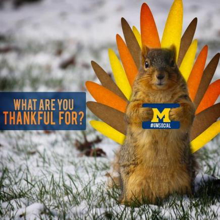 "Squirrel with turkey feathers holding a U-M Social sign with a ""what are you thankful for?"" graphic on the left of the squirrel."