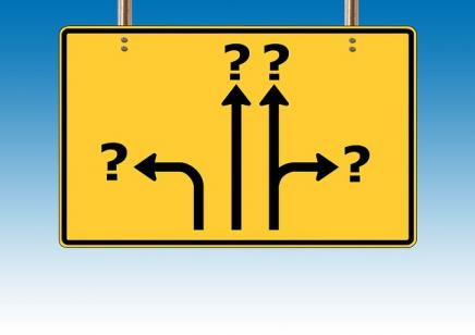 Bright yellow road sign with arrow pointing in different directions, all of the arrows are pointed toward question marks. There is a bright blue sky in the background.