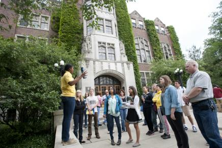Student standing on the stairs of the Michigan Union giving campus tour to a group of adults and students.