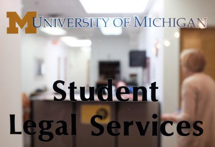 """View of the Student Legal Services office as you look through the clear glass of their door with """"Student Legal Services"""" written on the glass."""