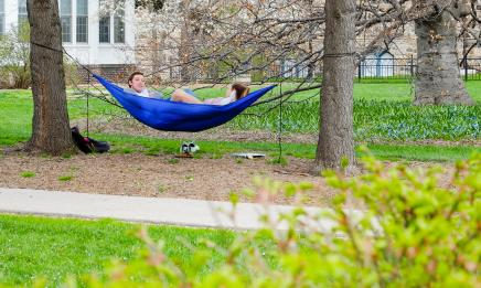 Man in woman lounging in blue hammock on campus