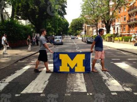 2 men carrying a Michigan flag on a street