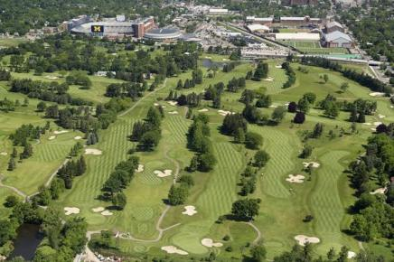 Aerial view of the Michigan Golf Course. There is a lot of green grass and several rows of trees. Buildings are seen in the distance.