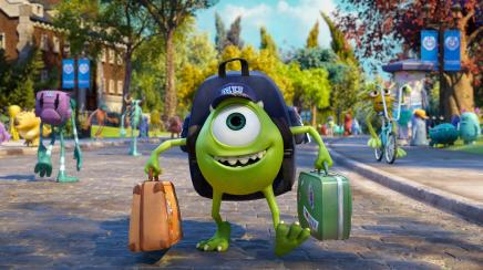 "Photo of Pixar's Monsters University character ""Mike Wazowski"" carrying luggage with campus in background."