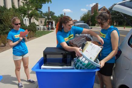 Students moving items from the blue move out bins to put the items in their cars.