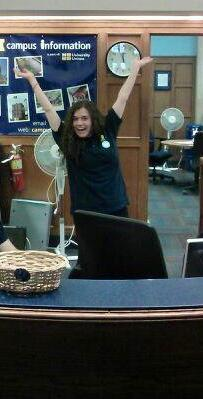 Student posing for Campus Information looking excited with arms in the air. Standing behind the campus information desk.