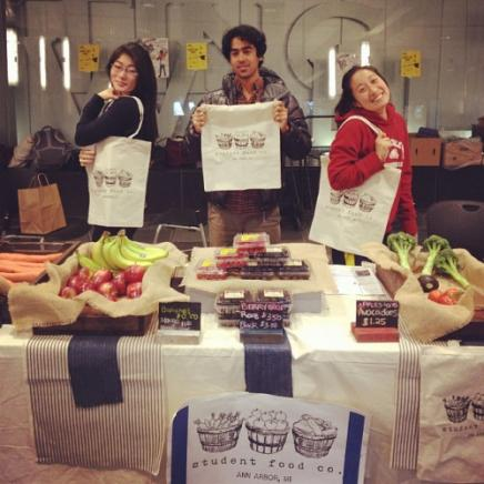 Three students holding Student Food Co. bags with fresh fruits and vegetables available on their food stand.