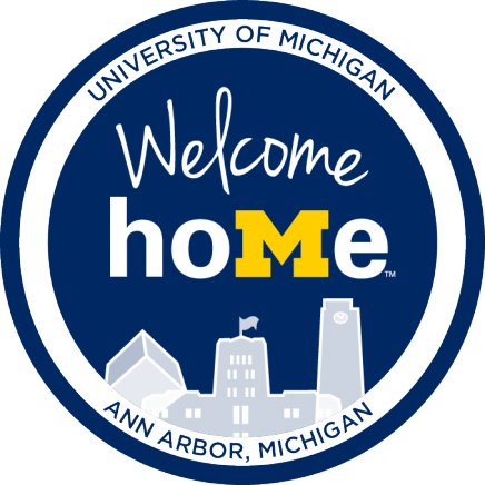 """Welcome Home"" logo, dark blue circle with the ""M"" in HOME as a Michigan M. Beneath there is an outline of the Michigan Union"